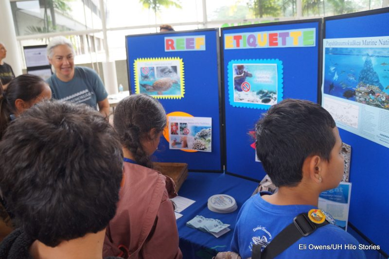 CHILDREN LOOKING AT POSTER DISPLAY ON REEF ETIQUETTE.
