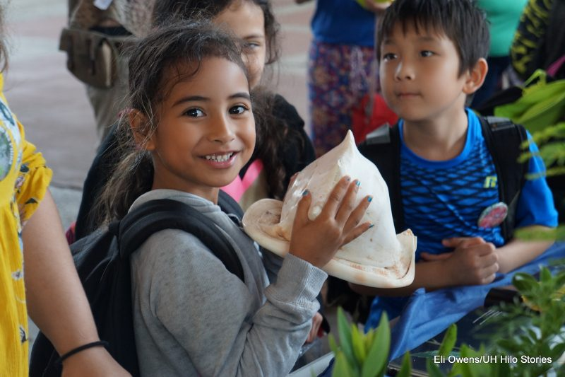 GIRL HOLDING LARGE CONCH SHELL.