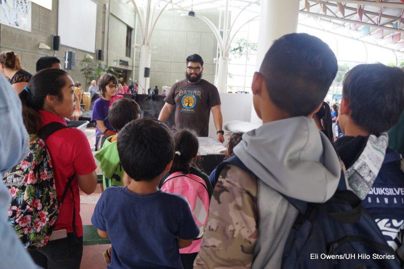 GROUP OF CHILDREN LISTENING TO MAN.