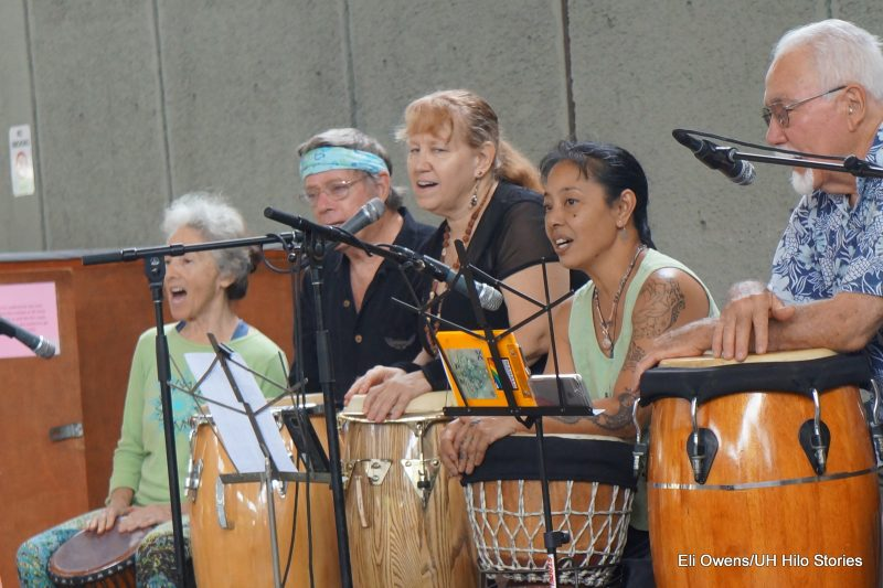 WOMAN SINGING AND PLAYING DRUMS.