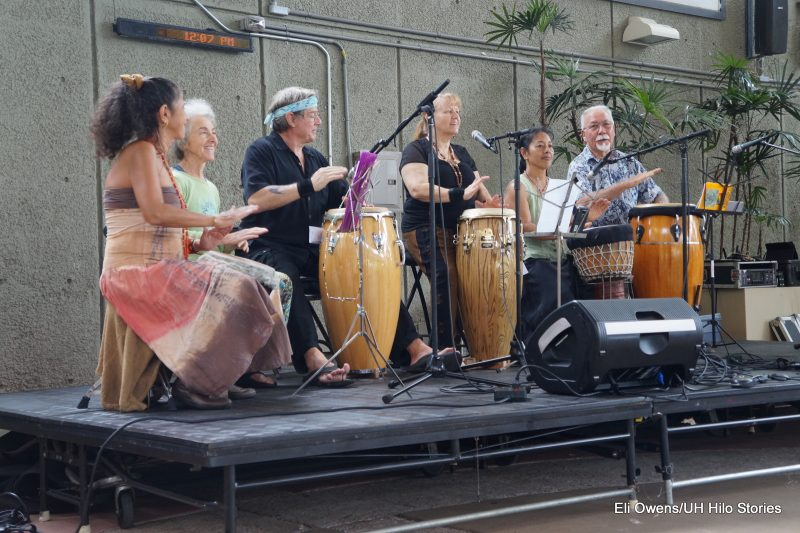 GROUP OF ADULTS SINGING, DRUMMING.