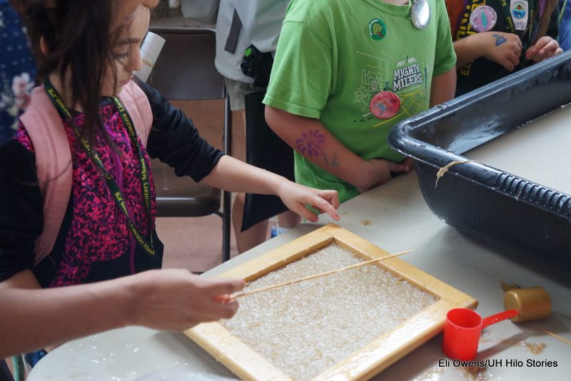 GIRL MAKING PAPER WITH PULP IN FRAME.
