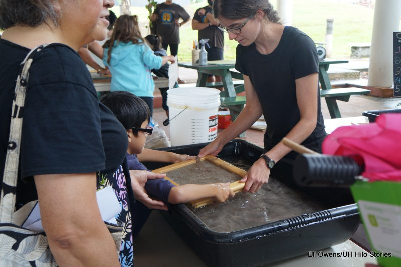 ADULTS HELP CHILDREN MAKING PAPER, WORKING IN TUB OF WATER.