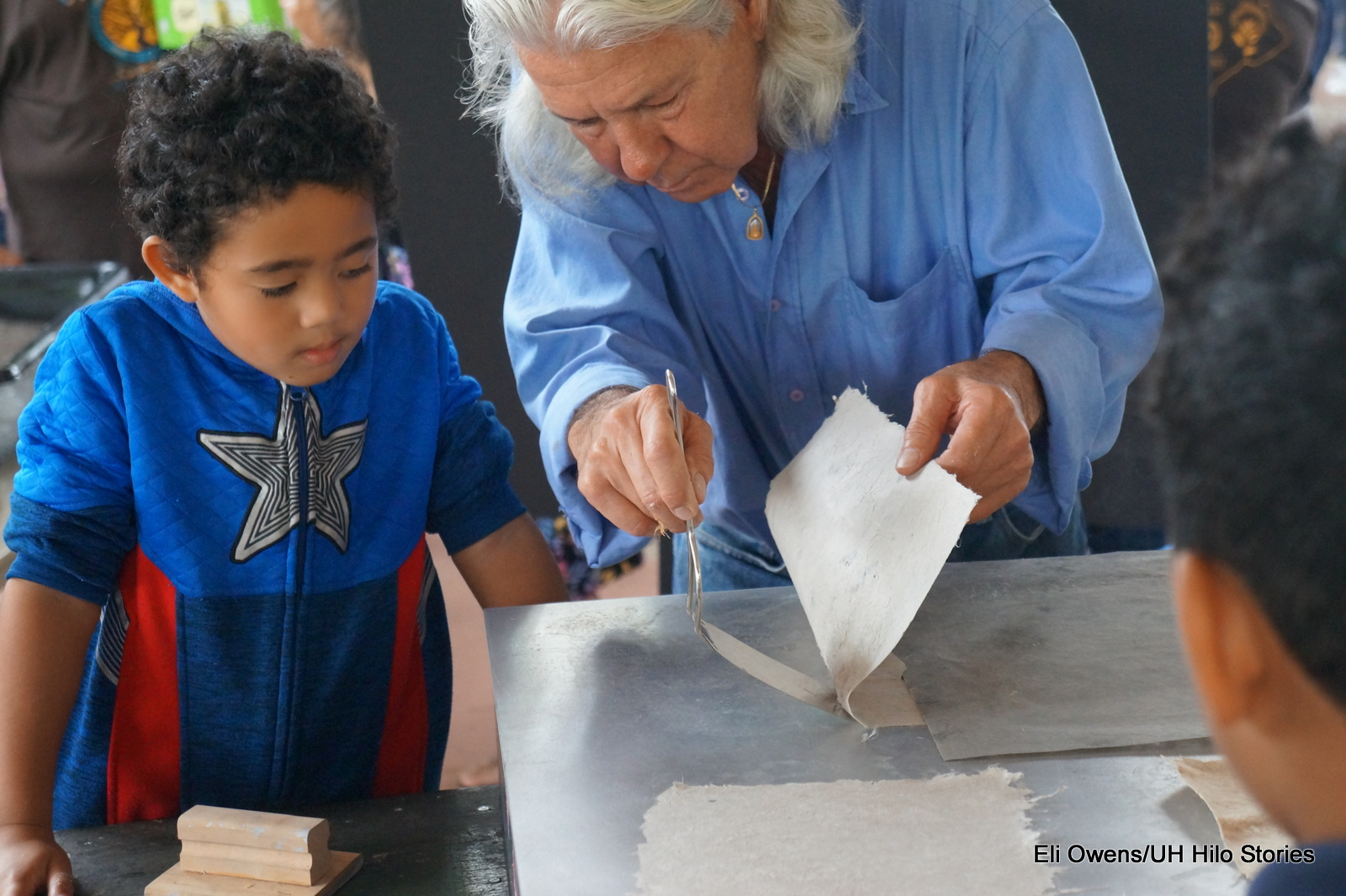 MAN HELPS CHILD WITH FINAL STEP OF PAPERMAKING.