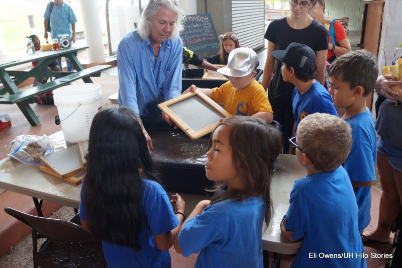 ADULT TEACHING CHILDREN TO MAKE PAPER, WORKING IN TUB OF WATER.