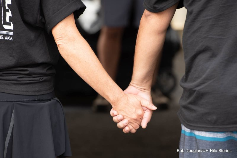 arms and hands of two people holding hands.