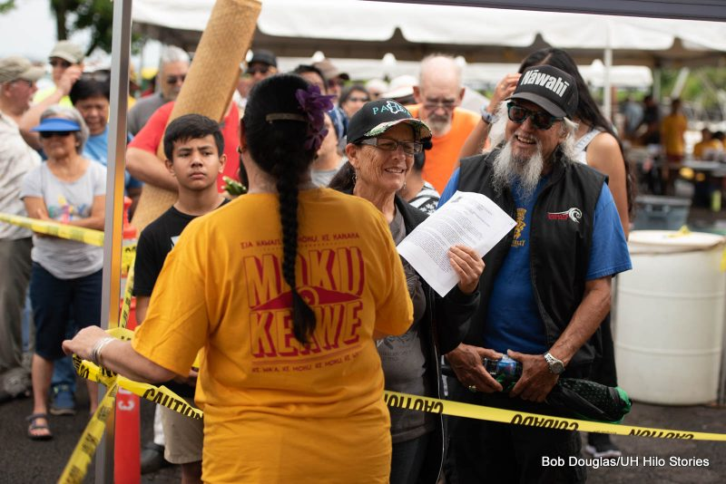 Woman talking to large group with the words on her t-shirt: MOKU KEAWE