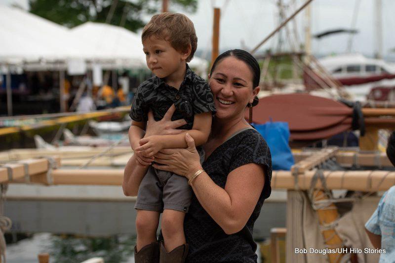 Woman holding child while on canoe.