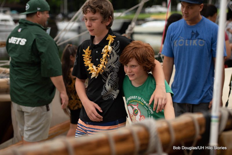 Two boys touring the canoe, arm in arm.
