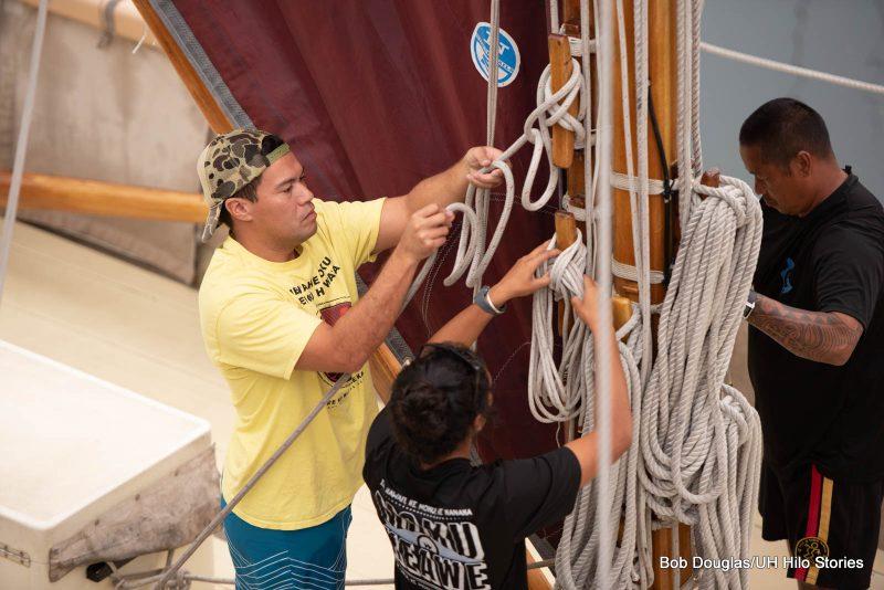 Man tying down rigging on mast.