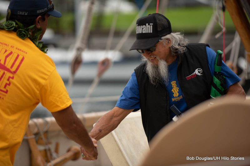 Two men shaking hands on the canoe.