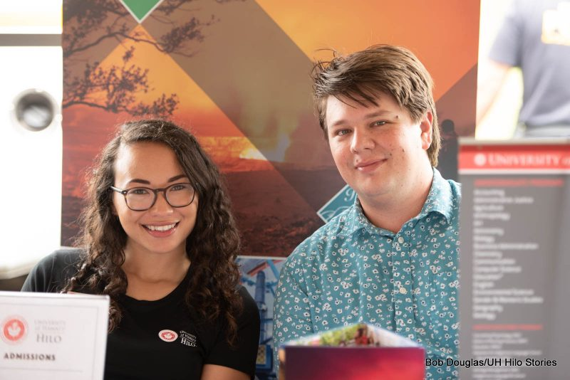 Two students from UH Hilo Admissions Office manning a booth at the event.