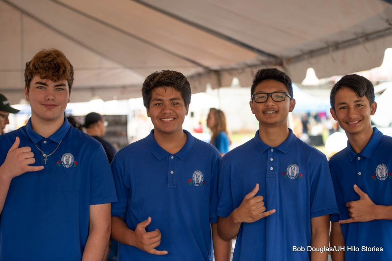 Four young men in t-shirts with Kamehameha Schools logo.