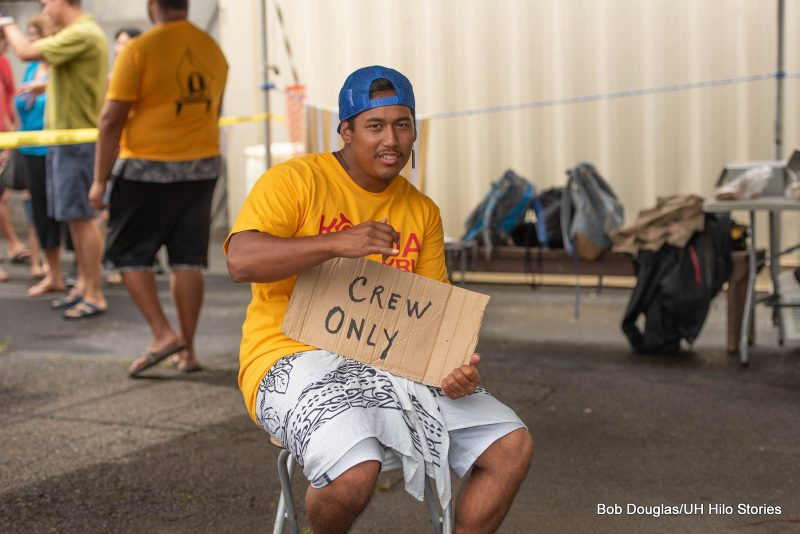 Man sitting holding a sign that reads Crew Only.