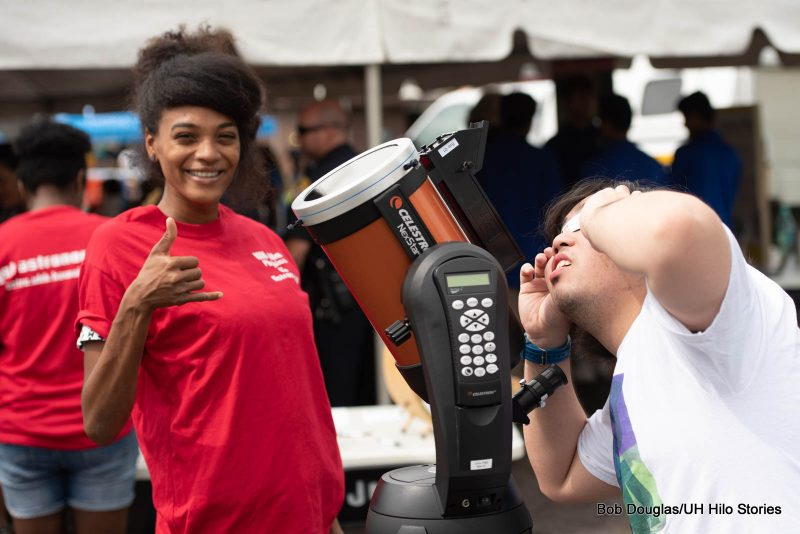 Woman in red giving shaka next to telescope.
