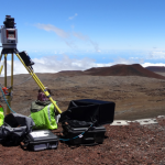 Two people doing research atop Maunakea, with equipment.