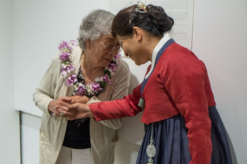 Seri and Mrs. Lauder who wears an orchid lei. The two are holding each other's hands and touching foreheads.