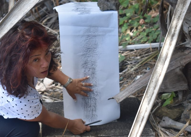 Seri is doing a rubbing of the words on a tombstone using a large sheet of paper and a charcoal pencil, which she holds in her right hand. She is turned, looking up at camera.