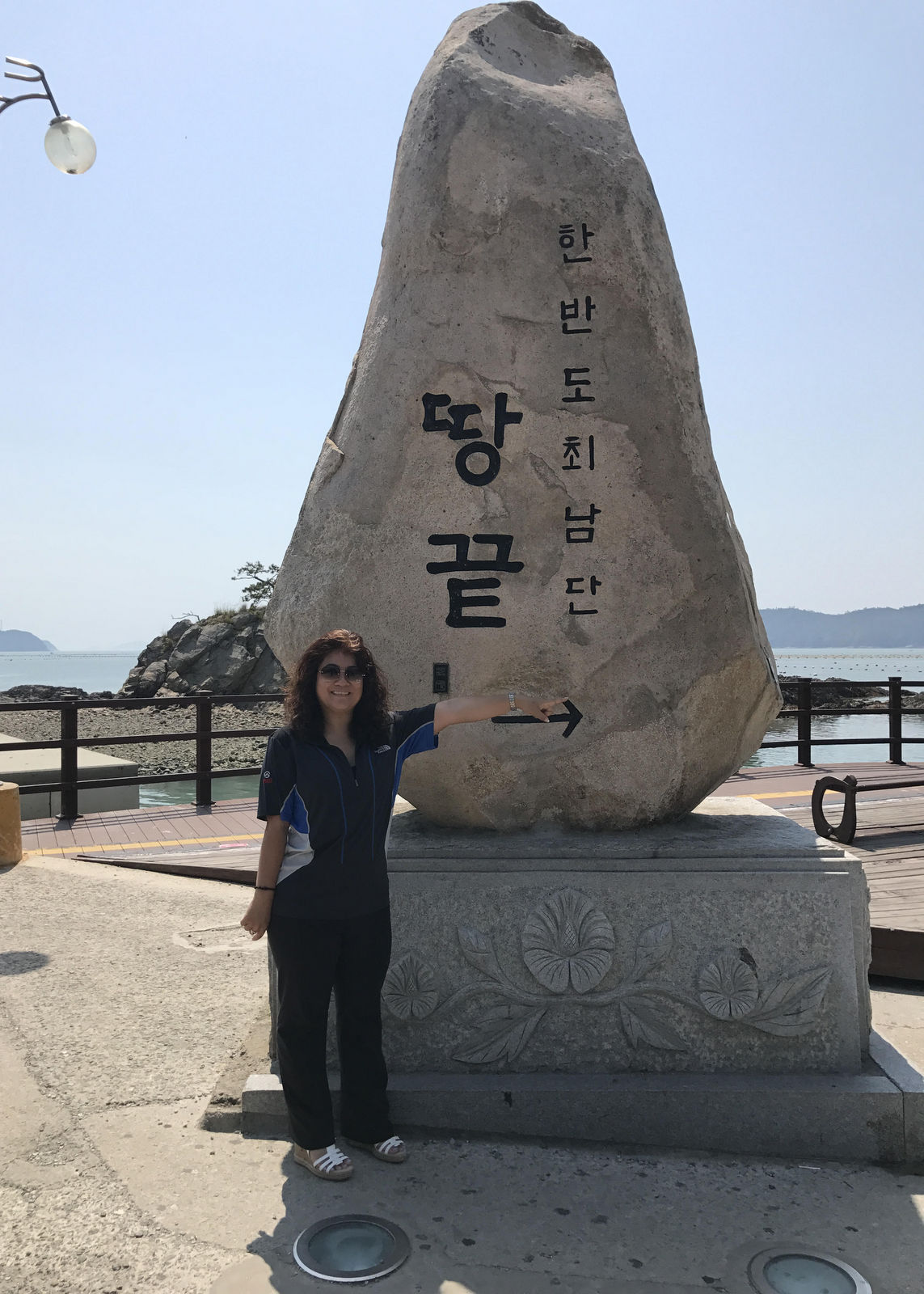 Prof. Luangphinith stands at a large stone marker with Lorean calligraphy. The sea is in the background.