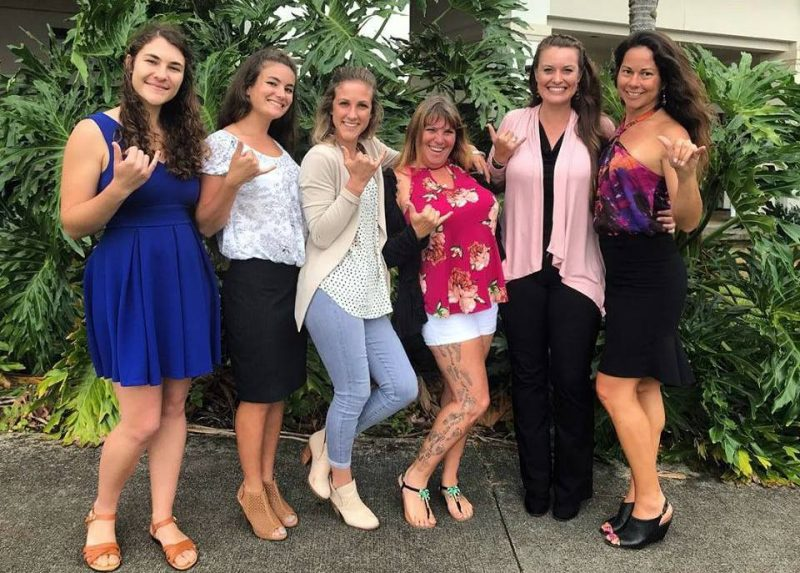 Gina Selig, Andrea Ehlers, Wheatley Crawley, Michelle Nason, Julia Stewart, and Nikola Rodriguez stand for group photo. All are giving the shaka.