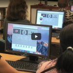 Still from video of students working on computers.