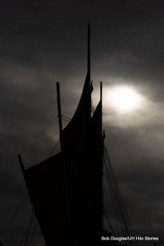 Sails of the canoe against a dark sky.