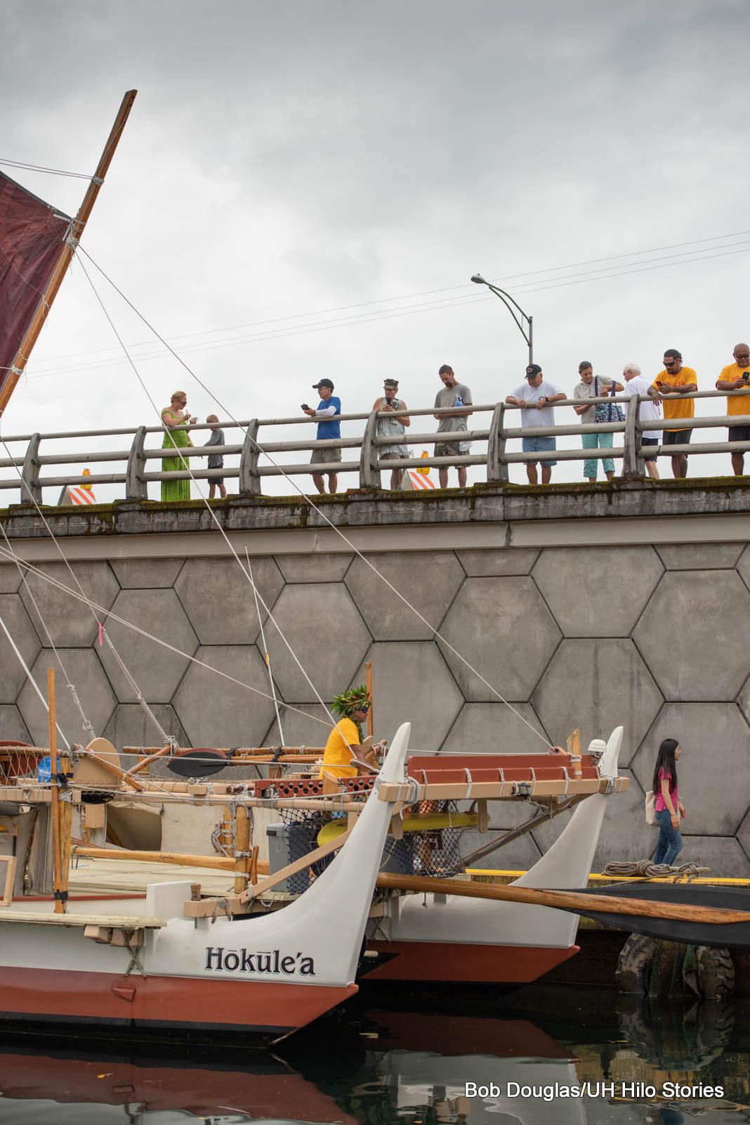 Hokulea docked near bridge, people up on bridge looking down on canoe.