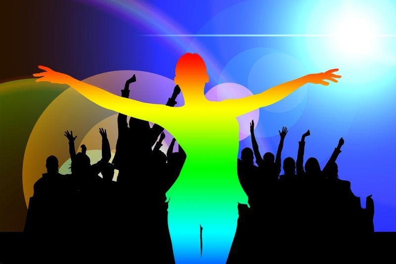 Silhouette of dancer in rainbow colors; Silhouette of crowd in background.
