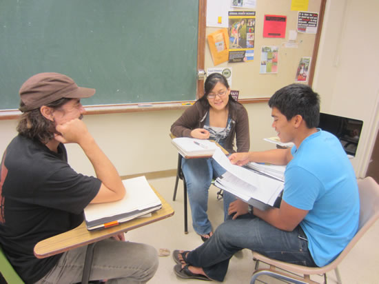 Three students sitting at desks, talking with each other with papers in front of them.