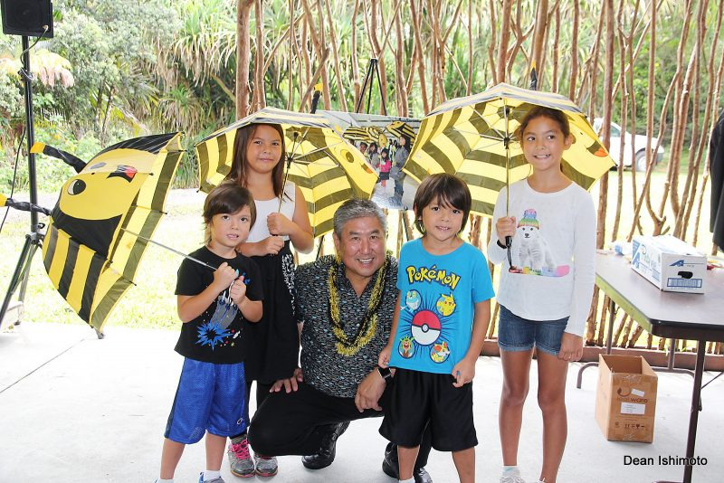 Alan Wong with group of schoolchildren who are holding umbrellas with bee motif.