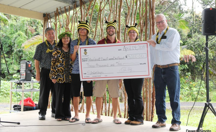 Group photo holding oversized check. Students have on hats with bee motif.