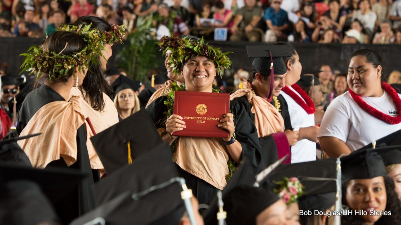 A graduate holds up a diploma.