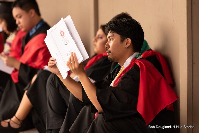 Graduate in regalia reading program.