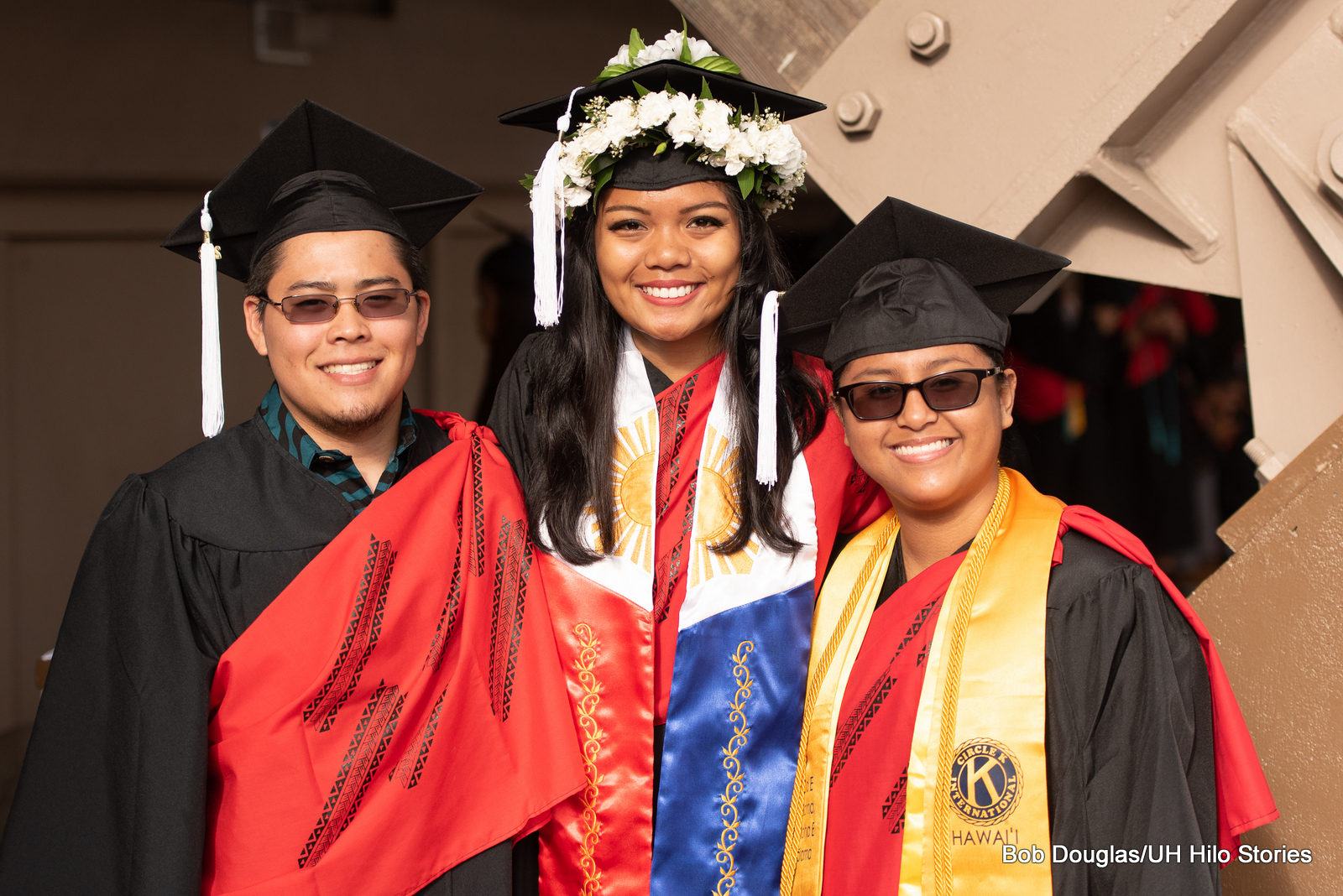 Three graduates in regalia, red, blue, and yellow sashes. Young woman in center has head lei wrapped around her cap.