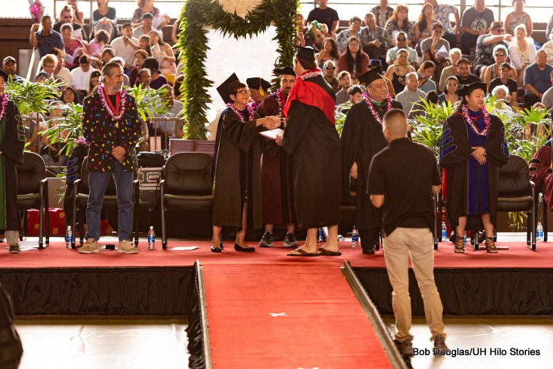 On the dais, chancellor shakes hand of graduate.