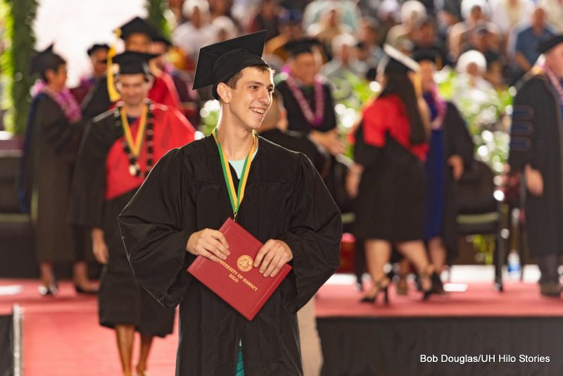 Graduate holds his diploma, looks to his left, smiling.