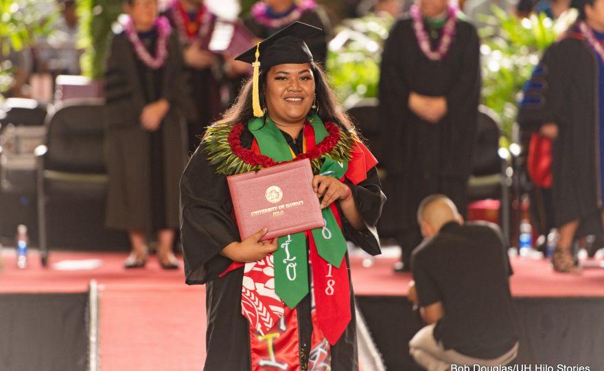 Graduate holding diploma.