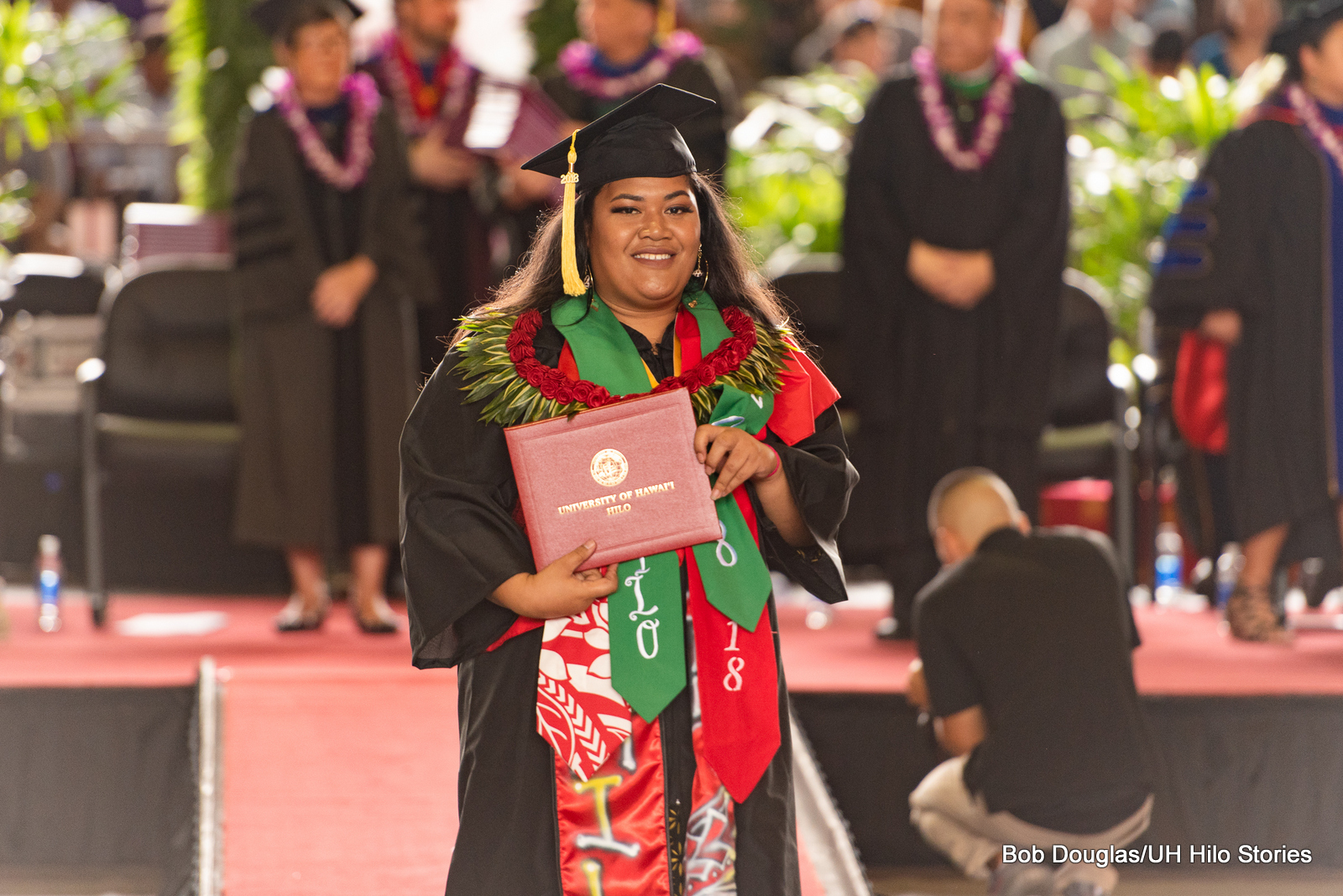 Graduate coming down from stage holding her diploma. She wears a green sash, red sashes, and lei.