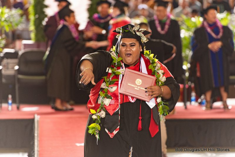 Graduate with diploma, wearing lei and red sash, she throws the shaka to the crowd..
