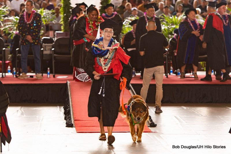 Graduate with dog by her side leaves the dais.