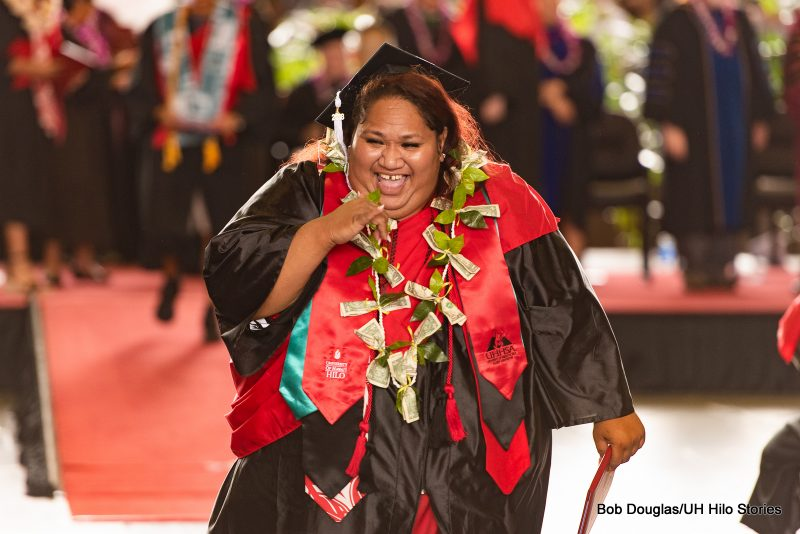 Happy graduate with money lei, holds diploma.