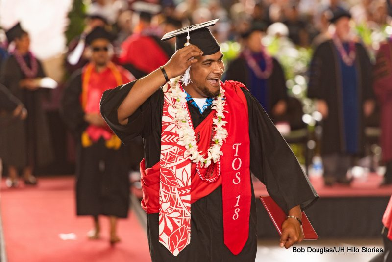 Graduate reaches up to tassel on his cap.