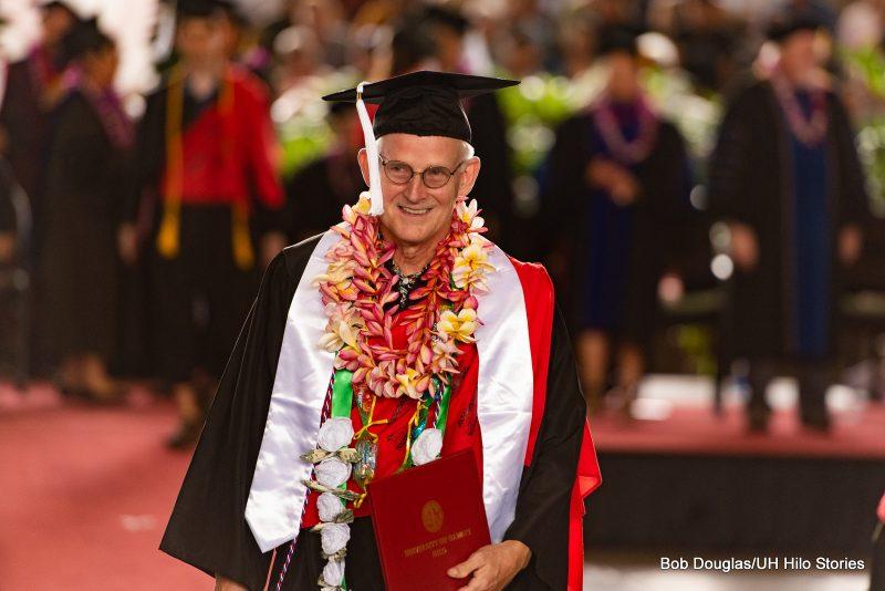 Older graduate with white sash, smiles, leaving dais.