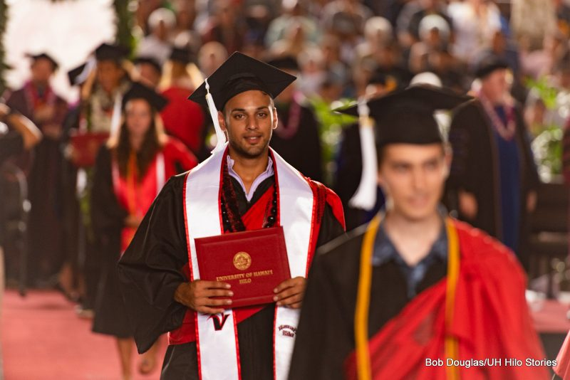 Graduate holds his diploma.