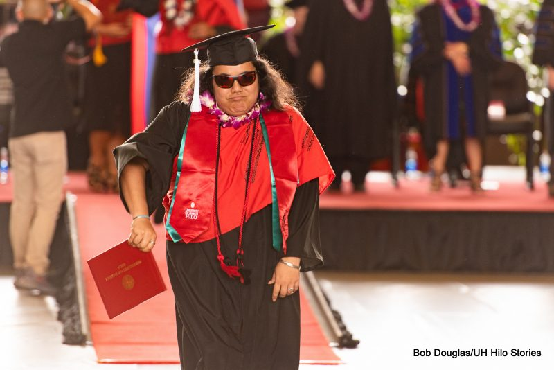 Graduate in sunglasses, holds her diploma off to the side. She wears a red cord..