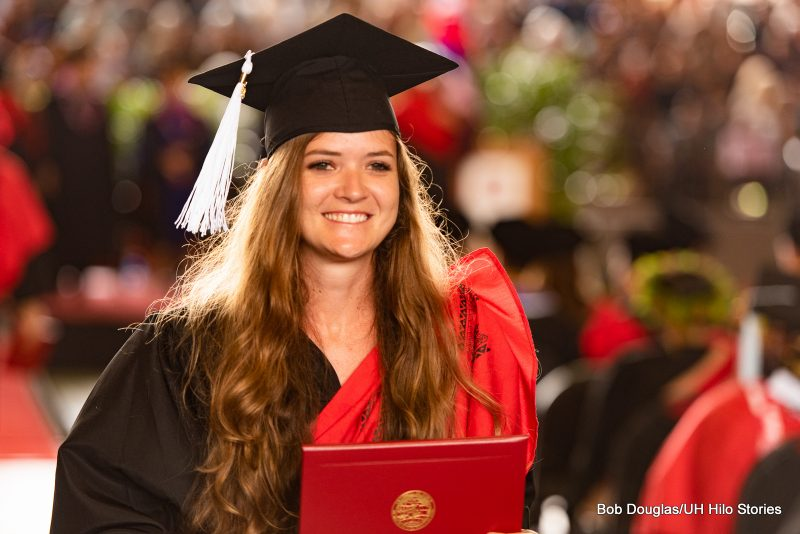 Graduate with long hair holds her diploma.