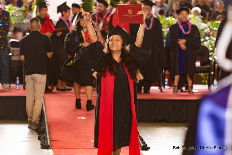 Graduate holds her arms high overhead in happiness.