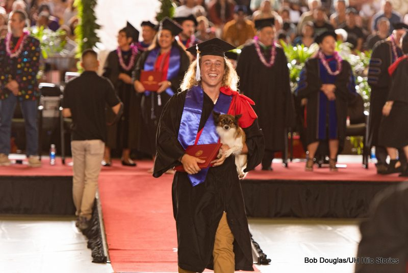 Graduate with long flowing hair leaves dais holding his little dog.