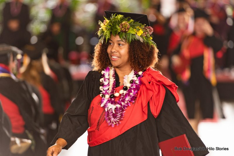 Graduate with thick floral lei on her cap, and wearing orchid lei, walks with her diploma.