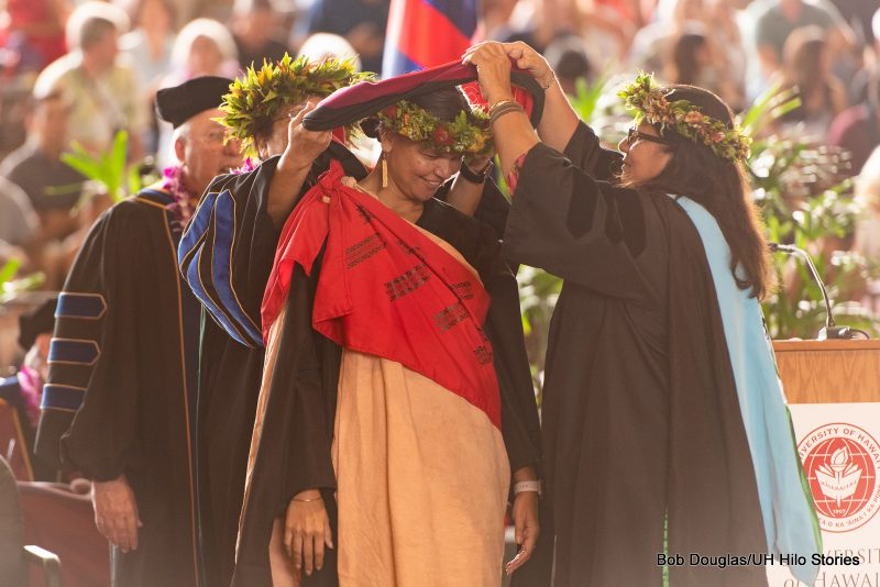 Graduate student bows head as two people place hood on her shoulders.
